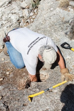 Bob, reaching down to clear a natural hole through the limestone shelf.