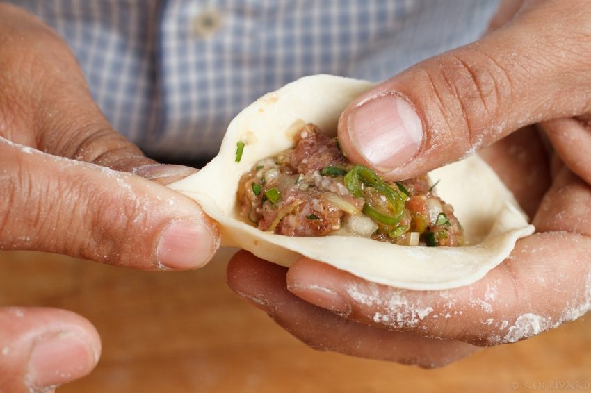 1. Place a spoonful of filling in round of dough.