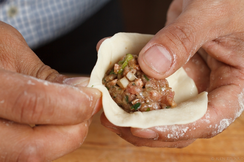 1. Begin with a spoonful of filling in a round of dough. For your first try use a bit less filling.