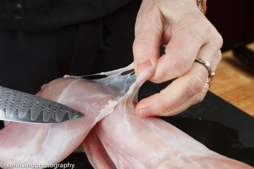 Remove the silver skin, either all in one step, or trimming as you ut the rabbit into smaller pieces.